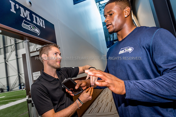 9/26/2016-- Renton, WA, USA<br /> <br /> <br /> Here: Karl Woll (left), account manager at Fatigue Science, helps to put one of his company&rsquo;s &lsquo;Readiband&rdquo; wristbands onto the wrist of Seahawks #86, Brandon Williams, age 28.<br /> <br /> <br /> Fatigue Science, a Canadian company, delivered &ldquo;Readiband&rdquo; sleep monitoring wristbands to several dozen NFL players on the Seattle Seahawks team at their training facility, the Virginia Mason Athletic Center (VMAC), in Renton, WASH, near Seattle. The wristbands will record how long and how deeply the players sleep and teams will use the data collected to improve player performance.<br /> <br /> Photograph by Stuart Isett. &copy;2016 Stuart Isett. All rights reserved.