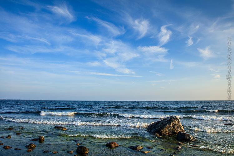 Vita vågor vid havsstrand med stenar I Stockholms skärgård.