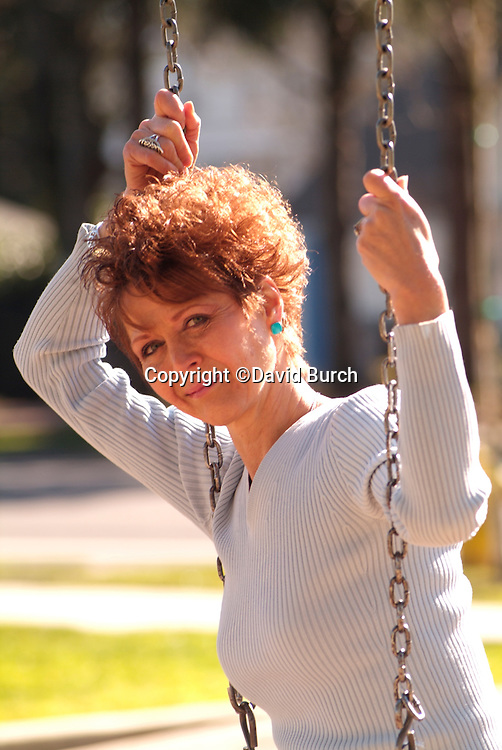 Redheaded woman on a swing in a park