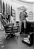 From behind his desk in the Oval Office in the White House in Washington, D.C., the camera sees United States President Gerald R. Ford on the phone and seated on the corner of his desk on August 11, 1974.  Note the open attache case full of papers in the foreground.<br /> Mandatory Credit: David Hume Kennerly / White House via CNP