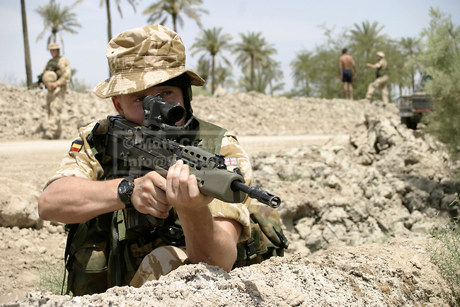 A British soldier keeps watch from behind a berm during a visit to a coalition funded irrigation project outside Basrah city,
