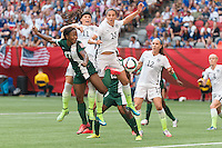 June 16, 2015: Francisca ORDEGA of Nigeria and Carli LLOYD of the USA jump for the ball during a Group D match at the FIFA Women's World Cup Canada 2015 between Nigeria and the USA at BC Place Stadium on 16 June 2015 in Vancouver, Canada. USA won 1-0. Sydney Low/Asteriskimages.com