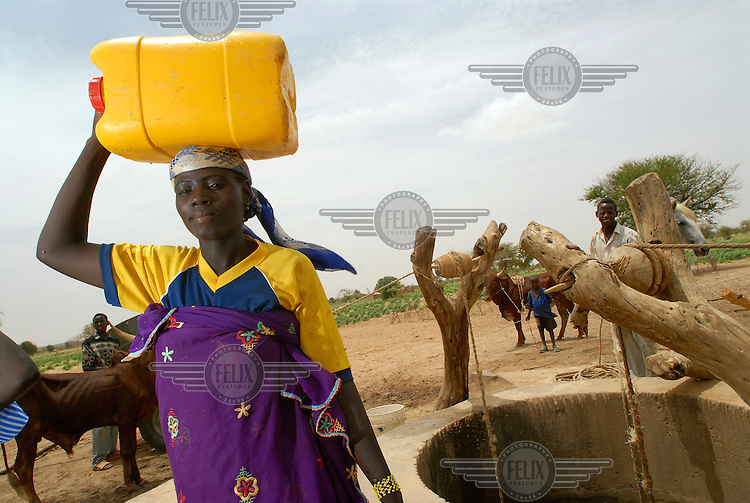 A young woman collects water from a well in Guidan Tanko.