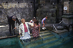 Holywell Pilgrimage on the feast day of  St Winefride. Holywell Flintshire Wales. Disabled woman  enters healing spring water, in hope of a cure. 1990s. <br />