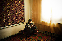 A man smokes in his home in Min-Kush. During the 1960s and 70s, Min-Kush was a prosperous city living off the wealth of uranium mining. It is now an impoverished and semi-deserted village of 2,500 people (down from a population of 20,000) polluted by uranium waste.
