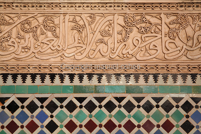 Detail of a cursive Kufic koranic inscription in carved stucco with zellige tiles below, in the central courtyard of the Al-Attarine Madrasa, a religious school built 1323-25 by the Marinid Sultan Uthman II Abu Said, who ruled 1310-31, in the medina of Fes, Fes-Boulemane, Northern Morocco. This courtyard has a central marble fountain, a zellige tiled floor and lower walls and intricate carved stucco and wooden walls with horseshoe arches and pillars. Cursive Kufic script is included in the tilework and stucco. The medina of Fes was listed as a UNESCO World Heritage Site in 1981. Picture by Manuel Cohen