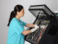 A healthcare professional operates a sterilization machine.