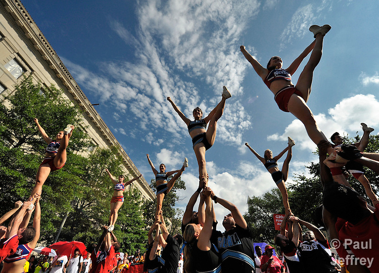 Cheerleaders perform as they and other people march through the streets of Washington, DC, on July 22, 2012, to demand that the U.S. and other governments keep their promises to fund global relief programs for those living with HIV and AIDS. The march took place as more than 23,000 delegates gathered in the US capital city for the XIX International AIDS Conference.