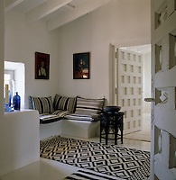 In this small sitting room the dark blue and white rugs and cushions punctuate an otherwise all-white space