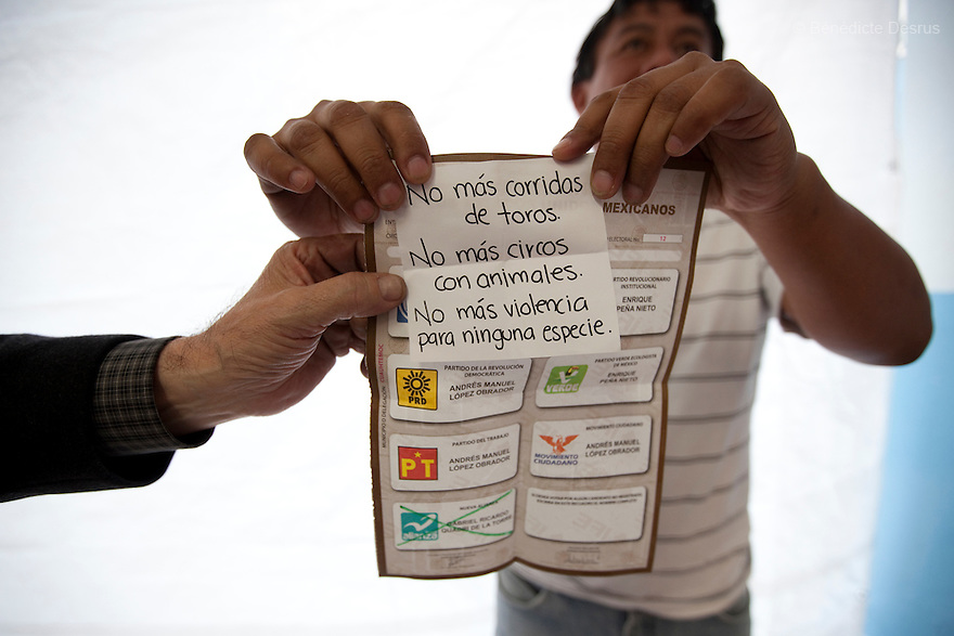 1 July 2012 - Mexico City, Mexico - An election worker shows a message left inside a ballot as he counts votes during the Mexico general election at a polling station in Mexico City. Mexicans vote for a new president on july 1. Photo credit: Benedicte Desrus