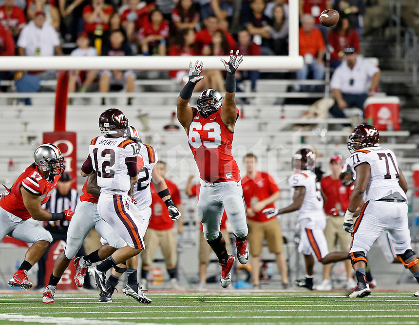 Virginia Tech Hokies quarterback Michael Brewer (12) throws a touchdown pass by the arms of Ohio State Buckeyes defensive tackle Michael Bennett (63) during the 2nd quarter of their game in Ohio Stadium on September 6, 2014.  (Dispatch photo by Kyle Robertson)