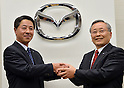 May 9, 2013, Tokyo, Japan - Outgoing President Takashi Yamanouchi, right, of Japan's Mazda Motor Corp., shakes hands with his successor, Masamichi Kogai, production and purchasing specialist of the automaker following a news conference in Tokyo on Thursday, May 9,m 2013. (Photo by Natsuki Sakai/AFLO)