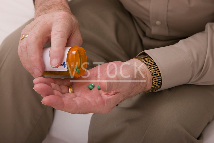 Senior man pouring pills from pill bottle, close-up of hands