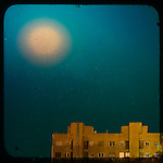The Moon shining in a blue sky over a block of flats
