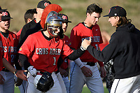 "Left fielder Jared Williams (1) of the North Greenville Crusaders wears the ""Crusader Crusher"" helmet placed on his head by teammates after he hit a two-run home run in the fifth inning of a game against the Palm Beach Atlantic Sailfish on Monday, February 25, 2019, at Ashmore Park in Tigerville, South Carolina. Palm Beach won, 7-5. (Tom Priddy/Four Seam Images)"