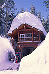 Clearing a driveway with a snow blower after deep winter snow covers homes in Lake Tahoe, California