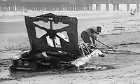 A treasure hunter uses his metal detector near a partially buried junk car deposited on the beach by a noreaster storm , Daytona Beach, FL, December, 1984. (Photo by Brian Cleary/www.bcpix.com)