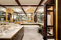 An opulent bathroom with two washbasins set in a chest of drawers unit. Mirrored walls give the room a sense of space.