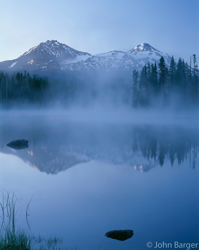 ORCAC_112 - USA, Oregon, Willamette National Forest, North (left) and Middle Sister (right) reflect in Scott Lake at sunrise while fog swirls above the lake.