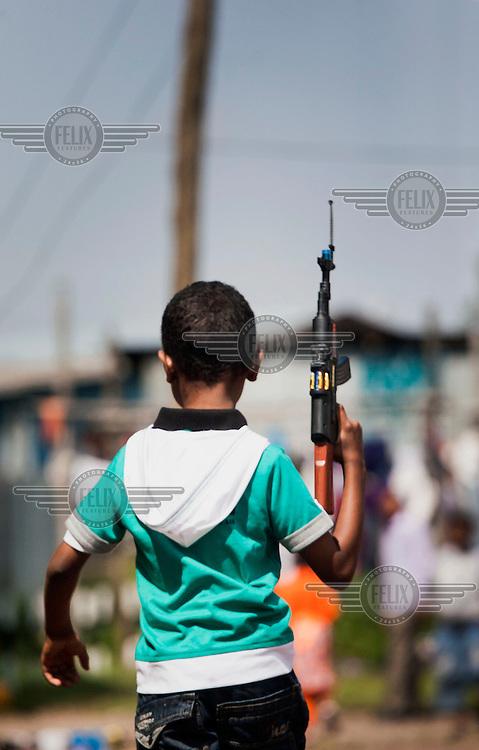 A boy holds a toy gun, a popular gift which children receive at the end of Ramadan, Eid Mubarak.