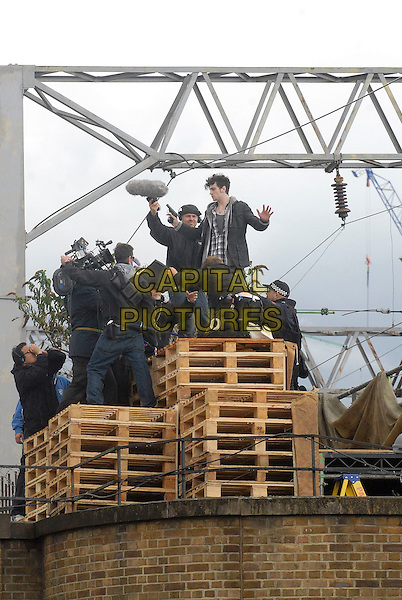"AARON JOHNSON.Filming on the set of ""Chatroom"", the new Hideo Nakata film, Camden Horse Market, London, England..July 29th, 2009.acting full length jeans denim black jacket pallet crew boom operator gun police officers profile .CAP/IA.©Ian Allis/Capital Pictures."