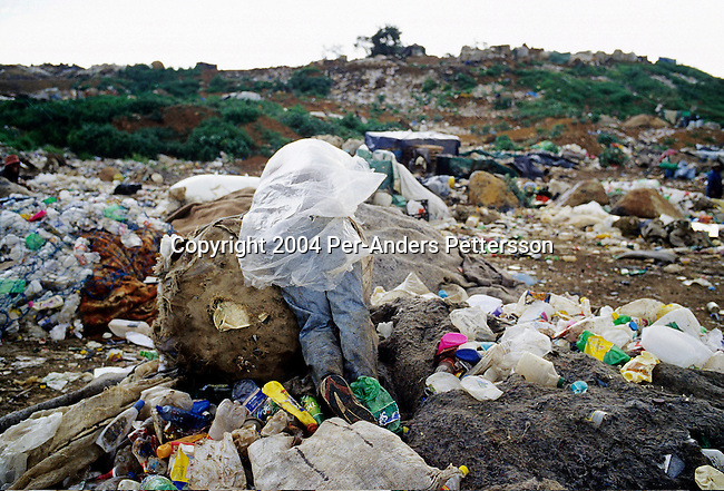 SOWETO, SOUTH AFRICA MARCH 6: An unidentified boy takes a break while collecting garbage on March 6, 2004 on a dump in Soweto, Johannesburg, South Africa. Hundreds of people make a living collecting trash at the dump. Plastic, paper and metals are collected and sold to buyers outside the dump. Soweto is South Africa?s largest township and it was founded about one hundred years to make housing available for black people south west of downtown Johannesburg. The estimated population is between 2-3 million. Many key events during the Apartheid struggle unfolded here, and the most known is the student uprisings in June 1976, where thousands of students took to the streets to protest after being forced to study the Afrikaans language at school. Soweto today is a mix of old housing and newly constructed townhouses. A new hungry black middle-class is growing steadily. Most residents work in Johannesburg but the last years many shopping malls has been built, and people are starting to spend their money in Soweto. .(Photo by Per-Anders Pettersson/Getty Images).