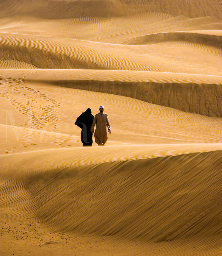 Couple walks in the desert.  Dubai. United Arab Emirates.