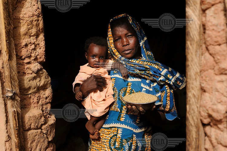 Gambo Outi, approximately 43, holding her eleven month-old daughter Ouma Salamatou, in a doorway at their home in the village of Koona. Gambo holds a bowl of millet which is often the only food that her family have to survive on each day. Ouma is suffering from malnutrition and is being monitored at the village's feeding centre.