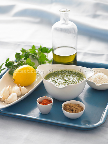 A blue tray with ingredients for a moroccan marinade. Includes bottle of olive oil, dishes of coarse salt, spices, garlic cloves, parsley sprig and lemon, with a bowl of sauce in center.