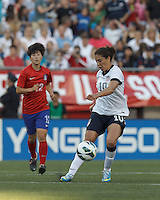 USWNT midfielder Carli Lloyd (10) passes the ball.  In an international friendly, the U.S. Women's National Team (USWNT) (white/blue) defeated Korea Republic (South Korea) (red/blue), 4-1, at Gillette Stadium on June 15, 2013.