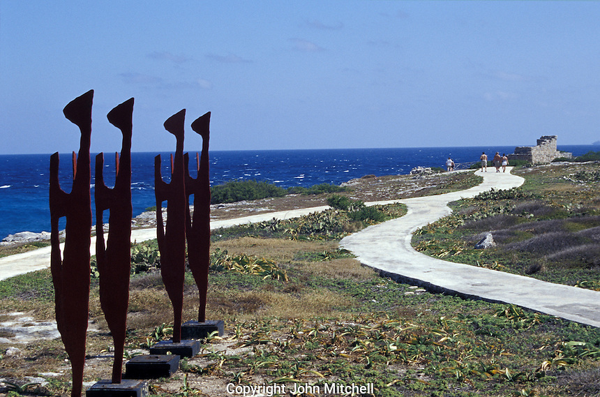 Punta Sur in El Parque Garrafon on Isla Mujeres, Quintana Roo, Mexico. This park has an open-air sculpture garden that opened in 2001. Sculptures by 23 Mexican and foreign plastic artists are on display. Also visible in this photo is an ancient  Mayan temple dedicatated to the fertility and moon goddess Ixchel.