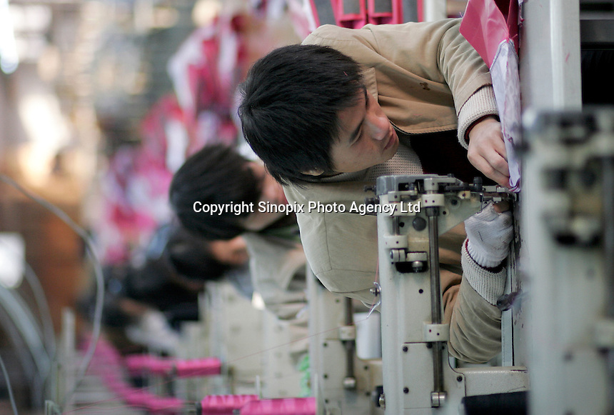 Workers on the assembly line at the Neo Bag Factory in Suzhou, Jiangsu Province, China. With an estimated 2,000 to 2,500 export manufacturers in the line, China is one of the worlds leading producers of leather bags and wallets with annual output at an estimated 800 Million pieces..
