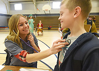 NWA Democrat-Gazette/FLIP PUTTHOFF <br /> ELLIS ISLAND REVISITED<br /> Whitney Goldthorpe (left), a Frank Tillery Elementary parent, plays the role of a nurse on Wednesday Feb. 6 2019 and gives her son, Austin Goldthrope, 8, a checkup during a program at the Rogers school about Ellis Island and immigration. Third-grade students, including Austin, acted as immigrants in 1910 and visited required stations to enter the United States, said Katelyn Fetner (cq), a teacher at Tillery. Teachers and parents staffed the stations for passport inspection, medical checkups, curency exchange, train tickets and other stops that were at Ellis Island. The island, in Upper New York Bay, was the gateway for over 12 million immigtrants to the United States from 1892 to 1954.
