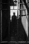 Silhouetted man in shadows through a rusted screen door.