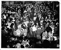 Dinner in the Grand Ballroom of the Chateau Frontenac, photograph, 1960s, from the Archives of the Chateau Frontenac, Quebec City, Quebec, Canada. The Chateau Frontenac opened in 1893 and was designed by Bruce Price as a chateau style hotel for the Canadian Pacific Railway company or CPR. It was extended in 1924 by William Sutherland Maxwell. The building is now a hotel, the Fairmont Le Chateau Frontenac, and is listed as a National Historic Site of Canada. The Historic District of Old Quebec is listed as a UNESCO World Heritage Site. Copyright Archives Chateau Frontenac / Manuel Cohen