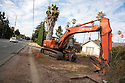 A tilted view of a large excavator in front of a house by a roadside, ready for demolition. This one-story house on a 10,000 square foot lot will be replaced with a 4,060 square foot two story single family home with an in-law unit. Cupertino, California, USA