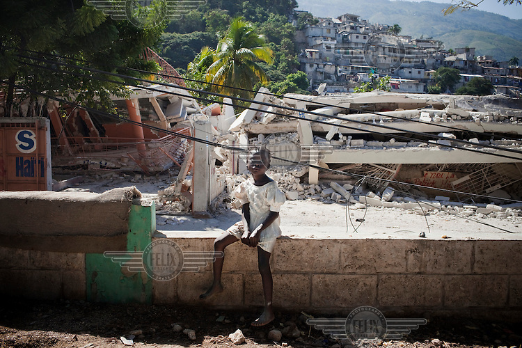 A girl sits in front of a collapsed building in Port-au-Prince. A 7.0 magnitude earthquake struck Haiti on 12/01/2010. Early reports indicated that more than 100,000 may have been killed and three million affected.