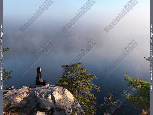 Young woman meditating, sitting on a rock with a mist covered lake in the background during sunrise