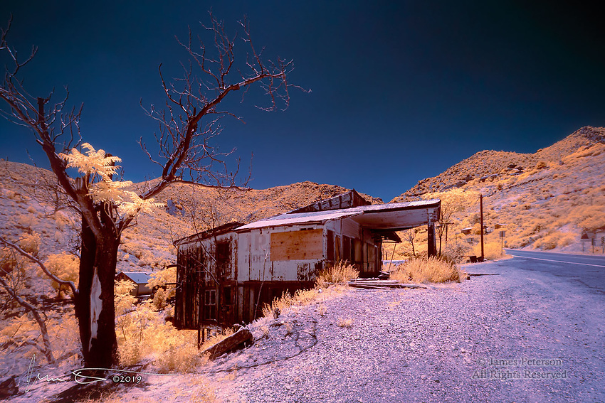 Ghost Station, Jerome, Arizona (Infrared).  Jerome is a historic mining town in the Black Hills of central Arizona.  In the 1950s, after the ore was depleted, it pretty much became a ghost town.  It was eventually resurrected as an artist and hippie colony, and more recently it has become a major tourist attraction.  But it still has plenty of ghosts, probably including a few inhabiting this abandoned gas station along the highway into town from the Verde Valley down below.<br /> <br /> Image ©2019 James D Peterson