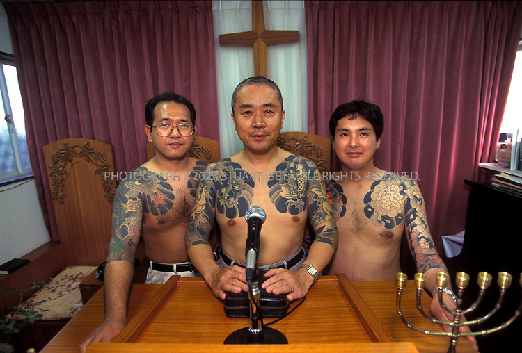 5/23/2000--Funabashi, Japan..Ex Yakuza gangster and born again Christian, Rev, Hiroyuki Suzuki (center). Body tattoos, chopped-off fingers and a criminal record have made the Rev Hiroyuki Suzuki into one of the most colourful and famous preachers in Japan, where barely 1 per cent of the population believes in Jesus. ..Suzuki, however, advocates in-your-face evangelism rather than Bible-study groups. Four years ago he and seven other former gangsters founded Mission Barabas, named after the thief Pontius Pilot freed instead of Jesus. Under the slogan, 'Our boss is God', they have adapted yakuza virtues of loyalty and discipline to their activities. Their territory is prisons and red-light districts. Among those drawn to their small chapel in Funabashi, west of Tokyo, are prostitutes, petty crooks and drug addicts. ..All photographs ©2003 Stuart Isett.All rights reserved.This image may not be reproduced without expressed written permission from Stuart Isett.