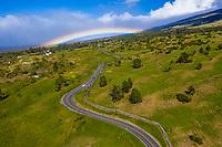A bright rainbow over a winding road through Ulupalakua Ranch, Maui.