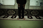 BAGHDAD, Iraq: 18th June 2014<br /> <br /> A man prays inside a Shiite mosque in Baghdad. Shia Muslims pray three times a day.  Unlike Sunni Muslims, Shia pray without folding their arms and use a clay tablet to rest their heads during prostration. <br /> <br /> <br /> Fixer: Haider Kata +9647704425647<br /> <br /> Ayman Oghanna for National Geographic