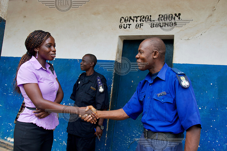 Baindu Koroma, a paralegal who works for Timap for Justice, greeting on-duty police officers on arrival at Bo central police station.<br /> Her work includes making regular visits to police stations, the prison, and the courts to monitor whether people are being afforded their lawful rights, for example, the right to bail, legal representation, detention without charge, etc, and if not to advocate on their behalf.