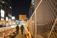 People walk under scaffolding near a construction site on Boylston street in the Fenway neighborhood of Boston, Massachusetts, USA, in the early hours of Saturday, Dec. 5, 2015.