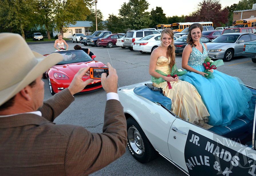 STAFF PHOTO BEN GOFF  @NWABenGoff -- 10/17/14 Danny Thomas takes pictures of his daughter Kamri Thomas, 16, left and fellow junior maid Bailie Ingraham, 17, as they prepare to ride into Huntsville's Eagle Stadium in a convertible during pre-game homecoming festivities before the football game between Lincoln and Huntsville on Friday October 17, 2014.