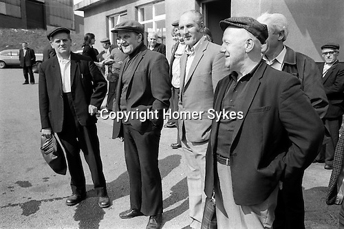 Outside the colliery miners waiting for transport to take them home. South Kirkby Colliery, Yorkshire England. Coal Miners story 1979. <br /> <br /> The four miners in the foreground waiting for the bus home, on the extreme left holding the bag is George Cutts and standing next to him (right of him as we see it) is his brother Laurence Cutts. Both were conveyor attendants underground. The building behind them is the Colliery Engineers and Records Office. In the background is the Ferrymoor Riddings Drift Mine.<br /> <br /> <br /> IF YOU KNOW THE NAMES OF ANY OF THE MEN IN THESE IMAGES PLEASE LET ME KNOW, I WOULD LIKE TO BE ABLE TO PUT A NAME TO A FACE. THANKS.