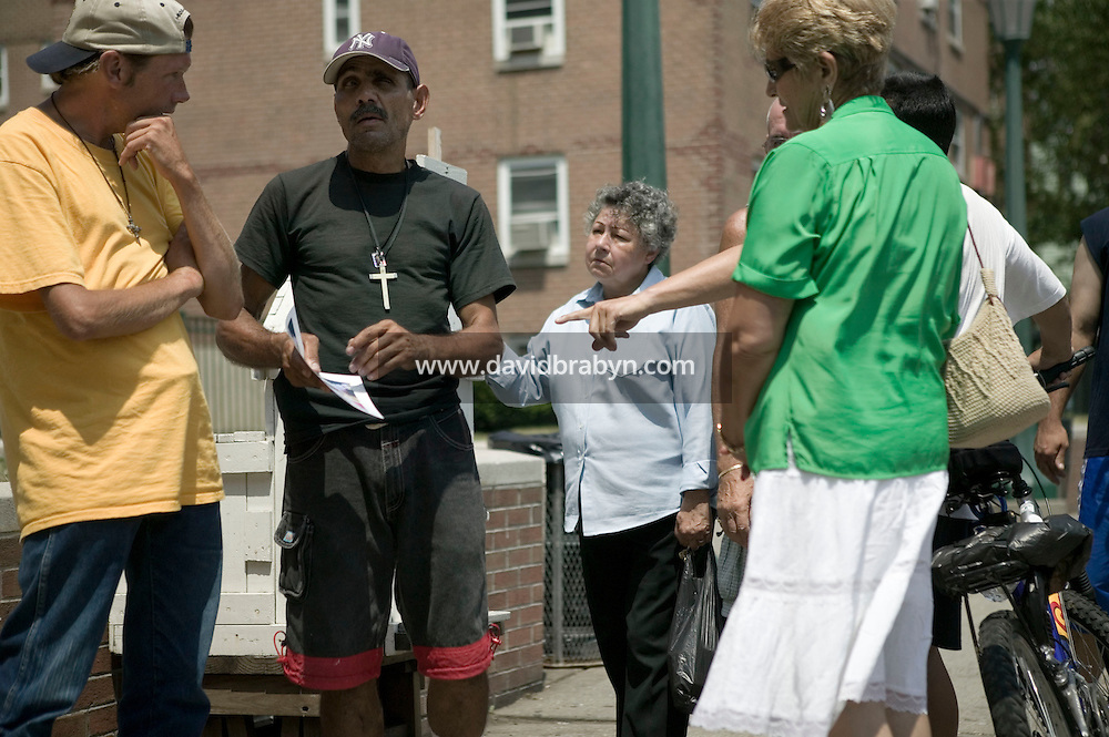 Local resident Julio Dones (2L), aka Sly, explains to people gathered in front of a statue of Christ that rests in a small shrine on Jackson and Third streets in Hoboken, NJ, USA, that the statue's right eye suddenly opened without human intervention a few days earlier in a sign from God, 31 July 2005. Photo Credit: David Brabyn