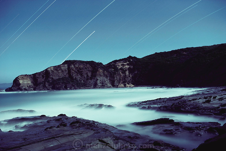 Long-exposure view of Dinosaur Cove by moonlight. The streaks in the sky are star trails created by the long time exposure. Dinosaur Cove, near Cape Otway, southern Australia is the world's first mine developed specifically for paleontology, normally the scientists rely on commercial mining to make the excavations. The site is of particular interest as the fossils found date from about 100 million years ago, when Australia was much closer to the South Pole than today. [1989].