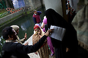 Polling officers instruct and offer help to local Kashmiri women who are seen going in to cast her vote amidst high security in the polling station in the Dal Lake area in Srinagar, summer capital of Jammu and Kashmir, India. A 50 hour curfew was imposed on May 5th to boycott the elections on May 7, 2009. ..Kashmir went into polls on the 4th round of Indian general elections. About 26 percent polling was recorded in the Indian parliamentary elections held in Kashmir on Thursday, May 7th 2009. The poll percentage was on the higher side this year as compared to 2004 polls when 15.04 percent polling was recorded.
