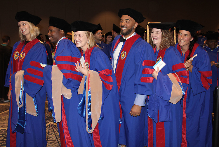The first graduating class earning a Doctorate of Business Administration from DePaul University — Karen Bartuch, left, Adam Cockrell, Kari Costello, Brandon Hendrix, Tammy Higgins and Erica Wagner — ham it up before heading into the commencement ceremony for the Driehaus College of Business June 10, 2018. (DePaul University/Carol Hughes)